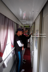 On the Trans Siberian RAilway, Passengers looking a t the list with the stops to see when we can stretch our legs.